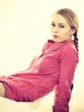 Mujer joven que miente en los pijamas que llevan de la cama Fotografía de archivo libre de regalías