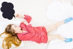 Mujer joven que miente en los pijamas que llevan de la cama Foto de archivo