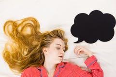 Mujer joven que miente en los pijamas que llevan de la cama Fotos de archivo