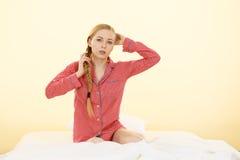 Mujer joven que miente en los pijamas que llevan de la cama Imágenes de archivo libres de regalías