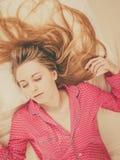 Mujer joven que miente en los pijamas que llevan de la cama Fotografía de archivo