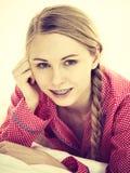 Mujer joven que miente en los pijamas que llevan de la cama Foto de archivo libre de regalías