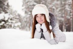 Mujer joven que miente en nieve Imágenes de archivo libres de regalías