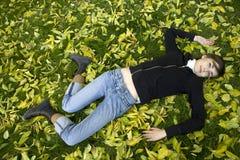 Mujer joven que miente en parque del otoño Imagen de archivo libre de regalías