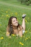 Mujer joven que miente en un campo con las flores Imagen de archivo