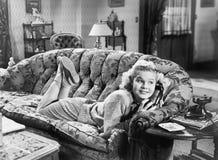 Mujer joven que miente en un sofá en una sala de estar y que habla en el teléfono (todas las personas representadas no son vivas  Fotos de archivo