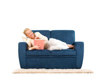 Mujer joven que miente en un sofá que come las palomitas Imagen de archivo libre de regalías