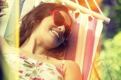 Mujer joven que miente en una hamaca en jardín Fotografía de archivo libre de regalías