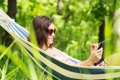 Mujer joven que miente en una hamaca en jardín con EBook. Fotos de archivo