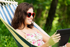 Mujer joven que miente en una hamaca en jardín con EBook. Imagenes de archivo