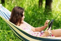 Mujer joven que miente en una hamaca en jardín con EBook. Imagen de archivo
