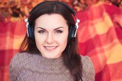 Mujer joven que miente en una manta en un parque del otoño y que escucha el th fotografía de archivo