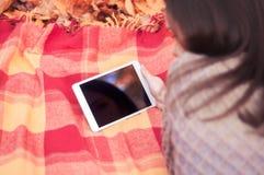 Mujer joven que miente en una manta y que usa la tableta foto de archivo