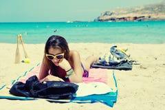 Mujer joven que miente en una playa hermosa Fotos de archivo libres de regalías