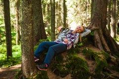 Mujer joven que miente en una roca en bosque Fotos de archivo