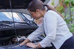 Mujer joven que mira abajo del motor de un coche Imagen de archivo