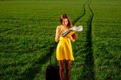 Mujer joven que mira al mapa en la pradera Imagen de archivo