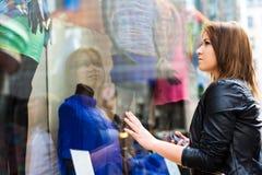 Mujer joven que mira anhelante la ropa Foto de archivo