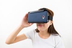 Mujer joven que mira con el dispositivo de VR Imagen de archivo libre de regalías