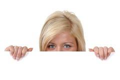 Mujer joven que mira con fijeza sobre el borde de una muestra en blanco Imágenes de archivo libres de regalías