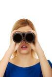 Mujer joven que mira con un binocular Foto de archivo