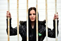 Mujer joven que mira de detrás las barras Imagenes de archivo