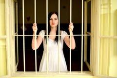 Mujer joven que mira de detrás las barras Imagen de archivo libre de regalías