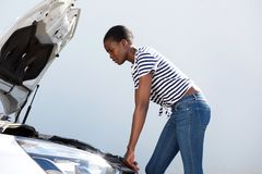 Mujer joven que mira debajo de la capilla del coche analizado en el camino Fotos de archivo libres de regalías
