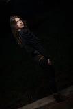 Mujer joven que mira detrás de su fondo del negro del hombro Imagen de archivo libre de regalías