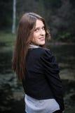 Mujer joven que mira detrás de su hombro y sonrisa Imagen de archivo