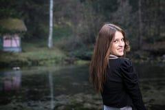 Mujer joven que mira detrás de su hombro y sonrisa Imagenes de archivo