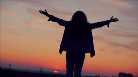 Mujer joven que mira el cielo la puesta del sol, muchacha acertada que piensa en vida en la naturaleza, disfrutando de la natural almacen de video