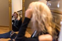 Mujer joven que mira el espejo Imagenes de archivo