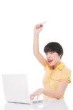 Mujer joven que mira el ordenador portátil chocado, sosteniendo la tarjeta de crédito Imagen de archivo