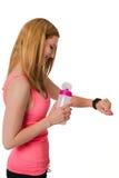 Mujer joven que mira el reloj digital con la botella Foto de archivo libre de regalías