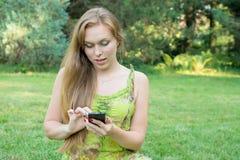 Mujer joven que mira el teléfono en la naturaleza Imagen de archivo