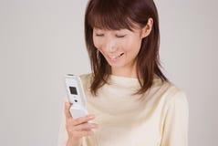 Mujer joven que mira el teléfono móvil Imagen de archivo