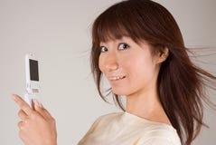 Mujer joven que mira el teléfono móvil Fotografía de archivo libre de regalías