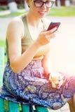 Mujer joven que mira el teléfono móvil Imagenes de archivo