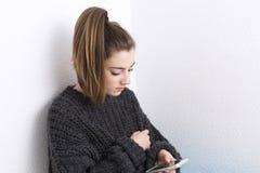 Mujer joven que mira el teléfono móvil en un fondo blanco Fotografía de archivo