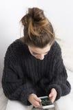 Mujer joven que mira el teléfono móvil en un fondo blanco Foto de archivo