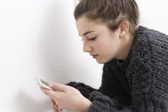 Mujer joven que mira el teléfono móvil en un fondo blanco Imagenes de archivo