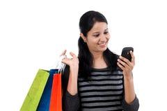 Mujer joven que mira el teléfono móvil y los panieres Fotografía de archivo libre de regalías