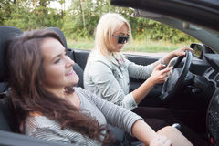 Mujer joven que mira el teléfono móvil y que monta el coche Fotografía de archivo