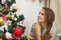 Mujer joven que mira en el árbol de navidad fotografía de archivo