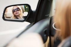 Mujer joven que mira en el espejo de coche Imágenes de archivo libres de regalías