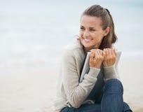 Mujer joven que mira en espacio de la copia mientras que se sienta en la playa Fotos de archivo libres de regalías