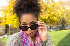 Mujer joven que mira a escondidas sobre las gafas de sol Fotos de archivo libres de regalías