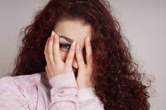 Mujer joven que mira a escondidas a través de los fingeres Imagen de archivo libre de regalías