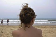 Mujer joven que mira fijamente el mar en la playa Fotografía de archivo libre de regalías